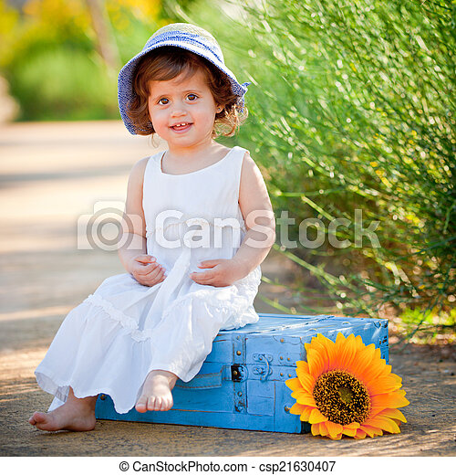 happy child sitting outdoors in summer - csp21630407