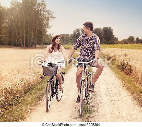 Happy couple cycling outdoors in summer - csp13005304
