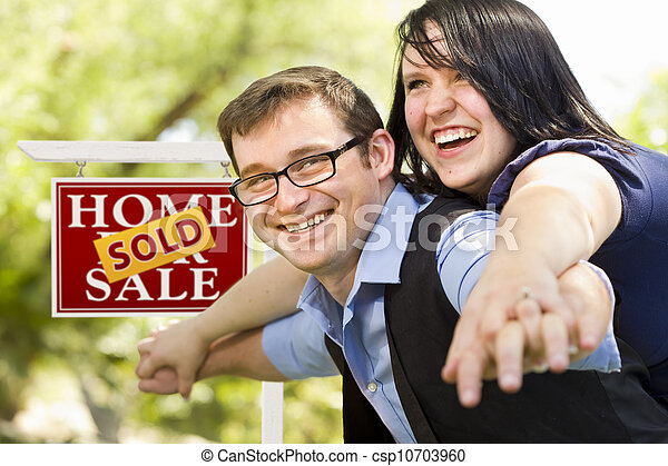 Happy Couple in Front of Sold Real Estate Sign - csp10703960