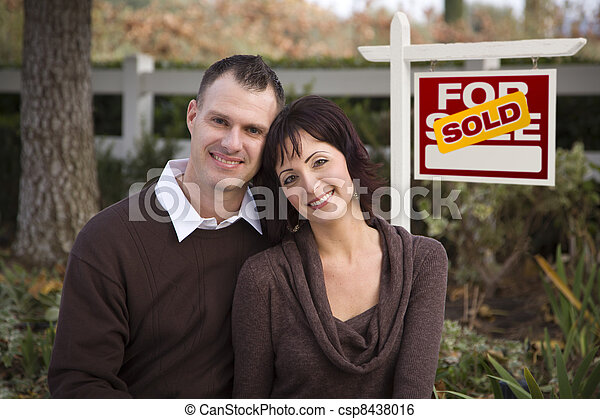 Happy Couple in Front of Sold Real Estate Sign - csp8438016