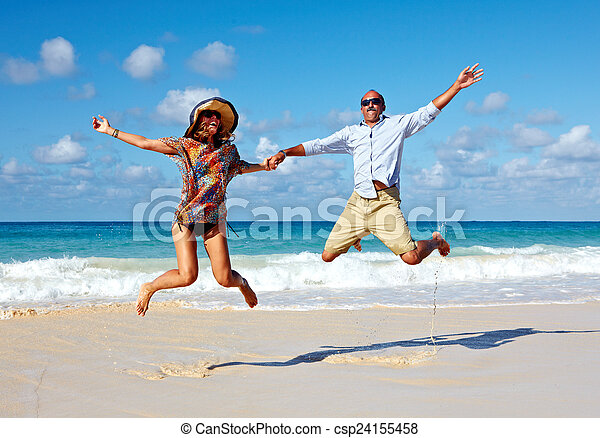 Happy couple jumping on the beach. - csp24155458