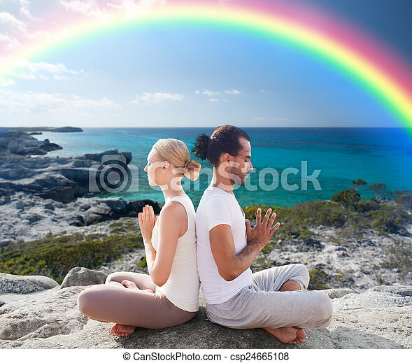 happy couple meditating in lotus pose on beach fitness