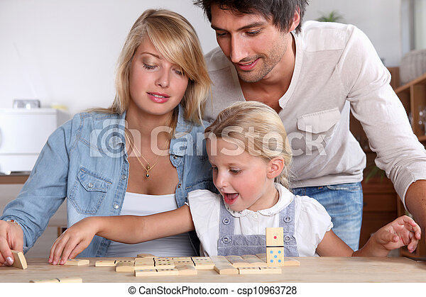 happy couple playing dominos with daughter - csp10963728