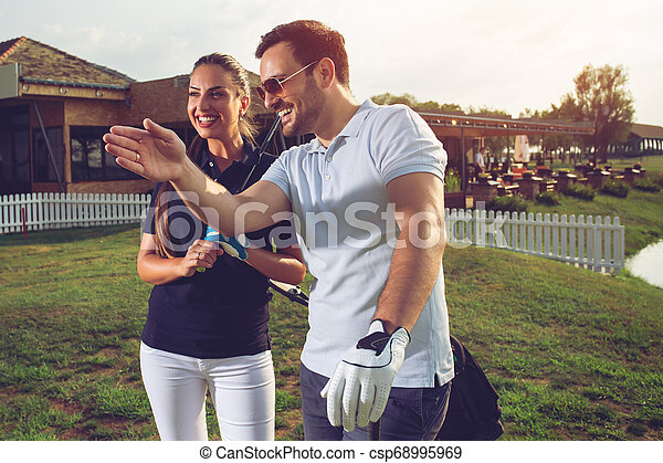 Happy couple playing golf at the club - csp68995969