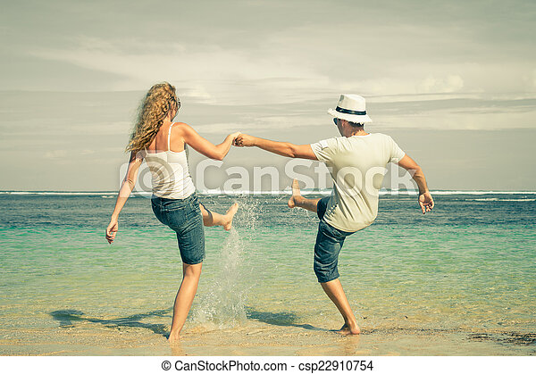 happy couple playing on the beach at the day time - csp22910754