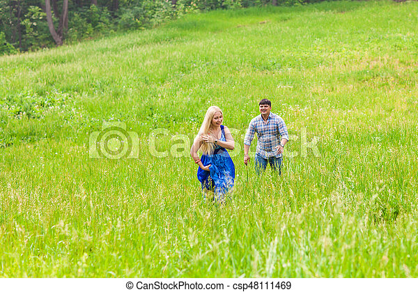 Happy couple running on a meadow in summer nature - csp48111469