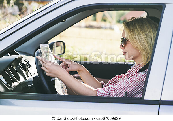 Happy couple traveling by car in nature and looking in map. Carefree friend travelers on countryside roadtrip journey. - csp67089929