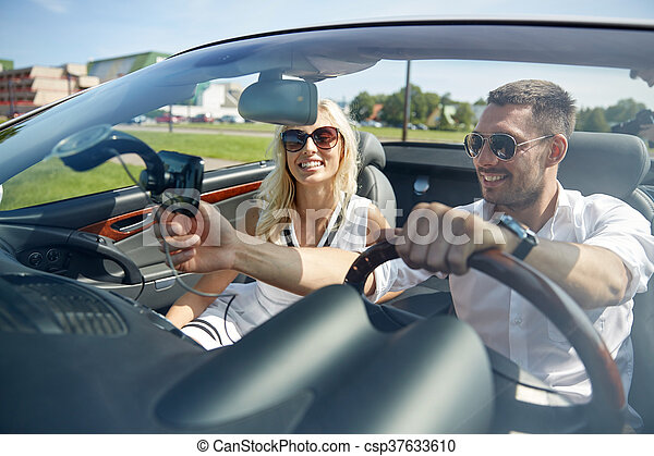 happy couple using gps navigator in cabriolet car - csp37633610
