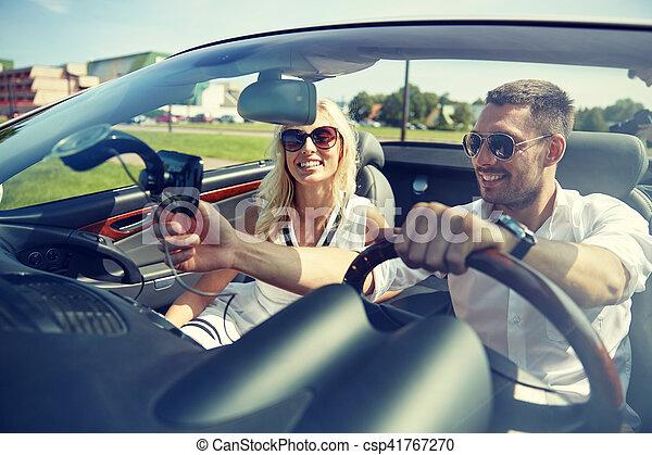 happy couple using gps navigator in cabriolet car - csp41767270