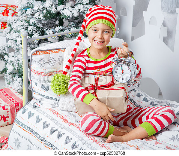 bd42eeec0484dd Happy cute little child boy dressed in striped pajamas sitting in decorated  New Year room at