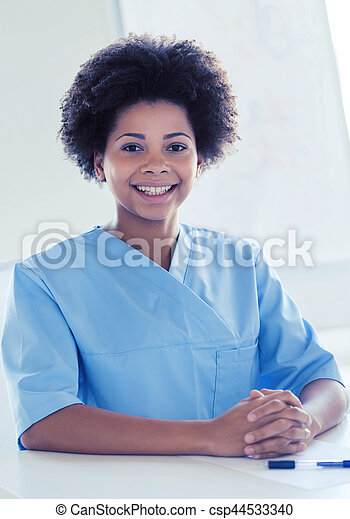 happy doctor or nurse with clipboard at hospital - csp44533340