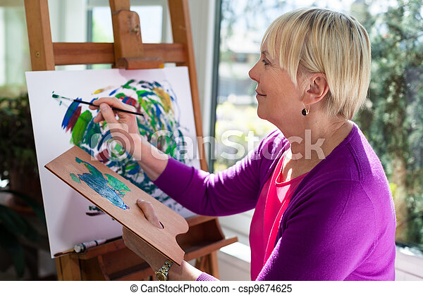 Happy elderly woman painting for fun at home - csp9674625