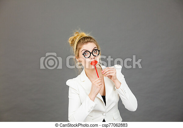 Happy elegant woman holding carnival accessoies on stick - csp77062883