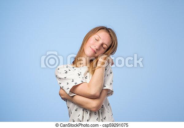 Happy european woman hugging herself with natural emotional enjoying face - csp59291075