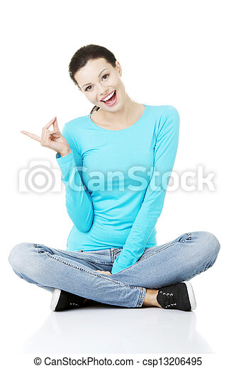 Happy , excited young woman pointing on copy space - csp13206495