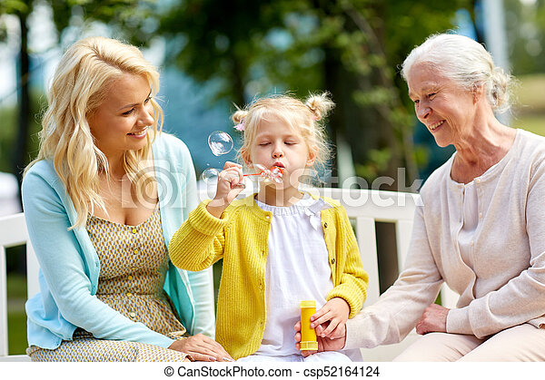 happy family blowing soap bubbles at park - csp52164124