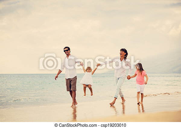 Happy Family have Fun Walking on Beach at Sunset - csp19203010