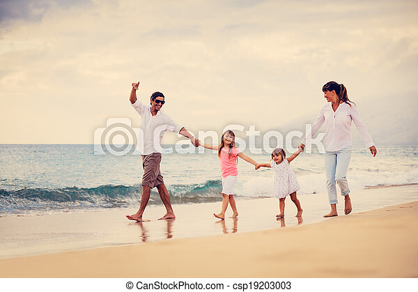 Happy Family have Fun Walking on Beach at Sunset - csp19203003