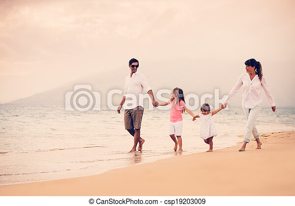 Happy Family have Fun Walking on Beach at Sunset - csp19203009