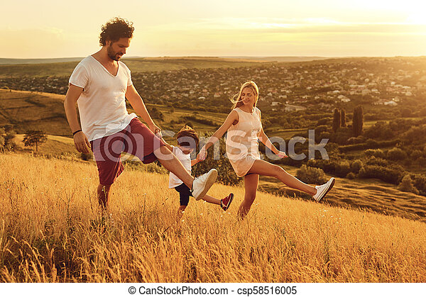 Happy family having fun walking in nature at sunset - csp58516005