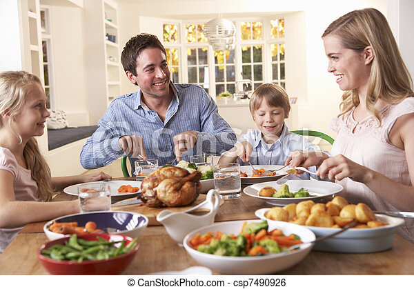 Happy family having roast chicken dinner at table - csp7490926