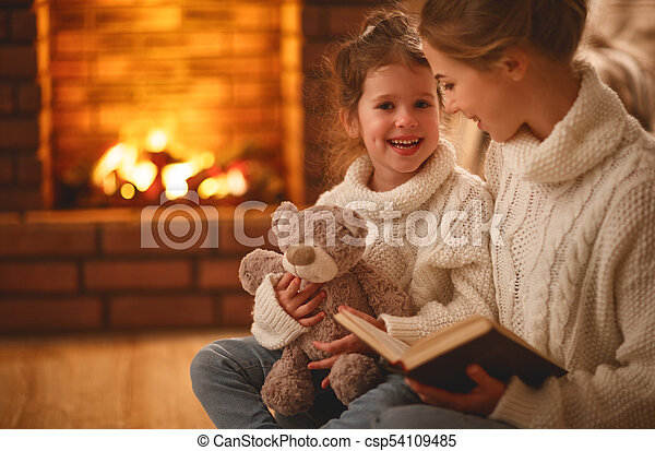 happy family mother and child daughter read a book on  winter evening - csp54109485