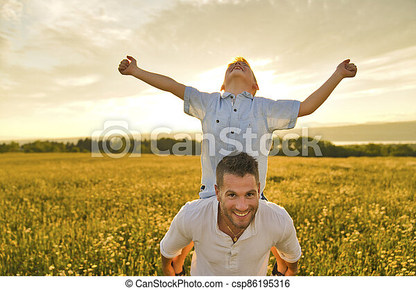 happy family of father and child on field at the sunset having fun on back with hand high - csp86195316