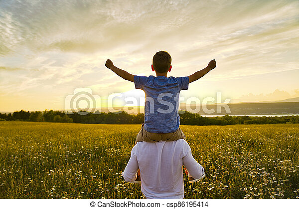 happy family of father and child on field at the sunset having fun - csp86195414