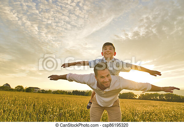 happy family of father and child on field at the sunset having fun on the father back - csp86195320