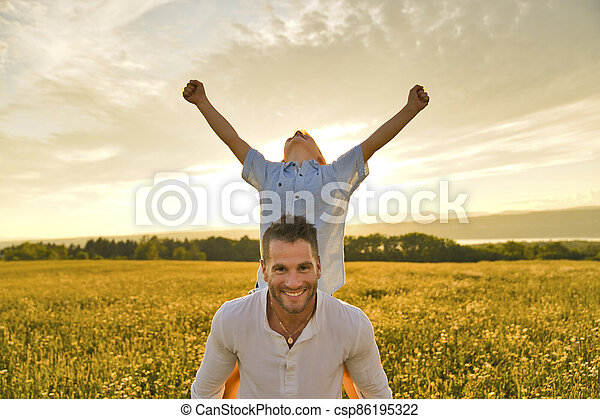 happy family of father and child on field at the sunset having fun on back with hand high - csp86195322