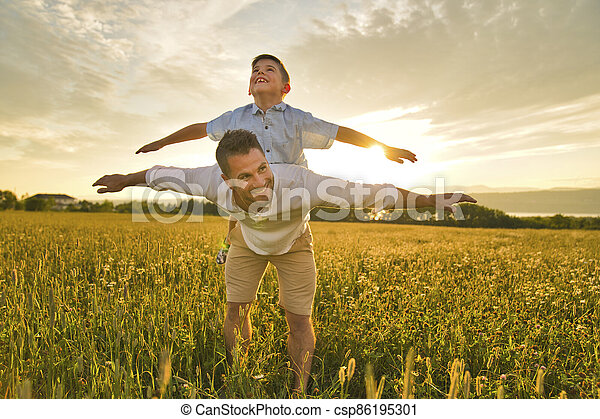 happy family of father and child on field at the sunset having fun on the father back - csp86195301