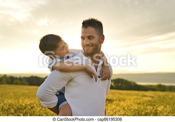 happy family of father and child on field at the sunset having fun - csp86195306
