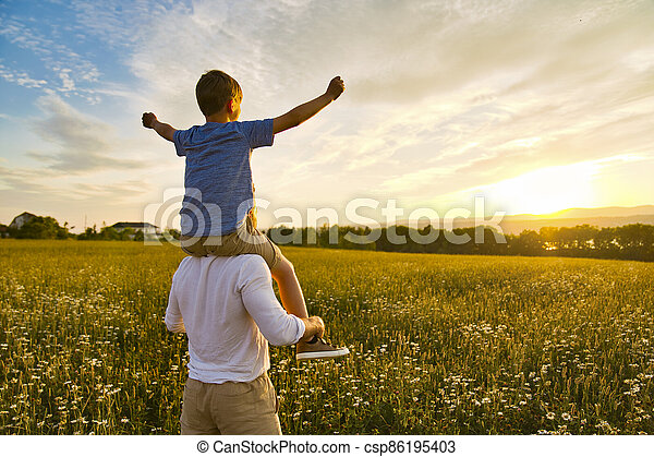 happy family of father and child on field at the sunset having fun - csp86195403