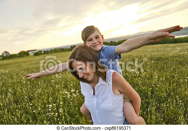 happy family of mother and child on field at the sunset having fun - csp86195371