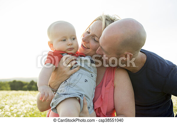 happy family of three. Father, mother and baby playing outside in summer at sunset time. - csp38551040