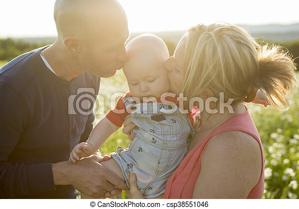 happy family of three. Father, mother and baby playing outside in summer at sunset time. - csp38551046