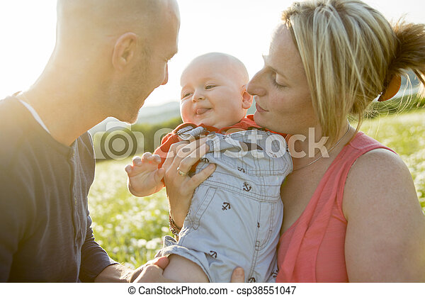 happy family of three. Father, mother and baby playing outside in summer at sunset time. - csp38551047