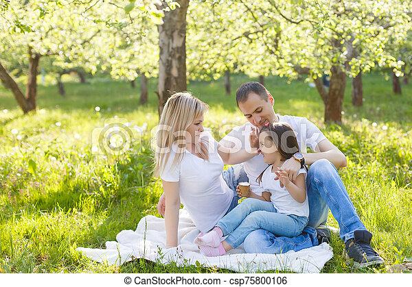 Happy family of three having fun in the park - csp75800106