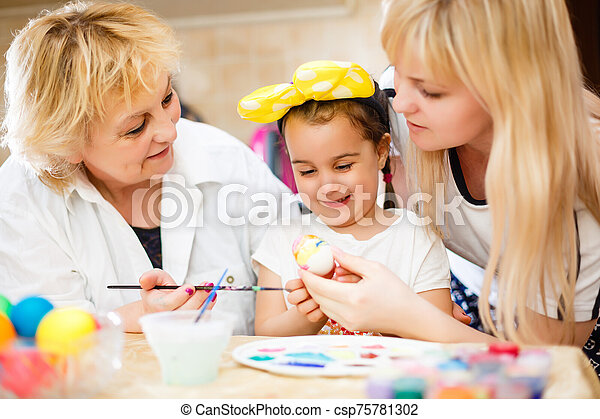 Happy family painting eggs for Easter - csp75781302
