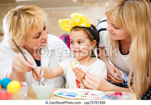 Happy family painting eggs for Easter - csp75781309