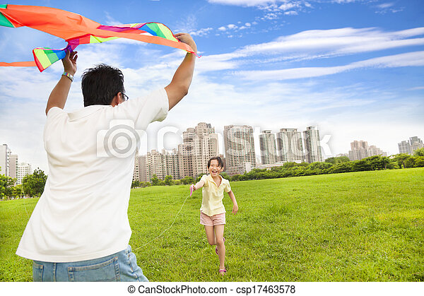 happy family playing colorful kite in the city park - csp17463578
