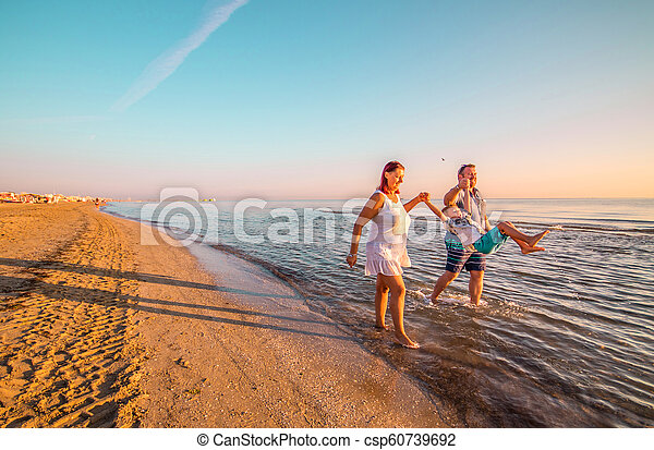 happy family playing on the shore - csp60739692