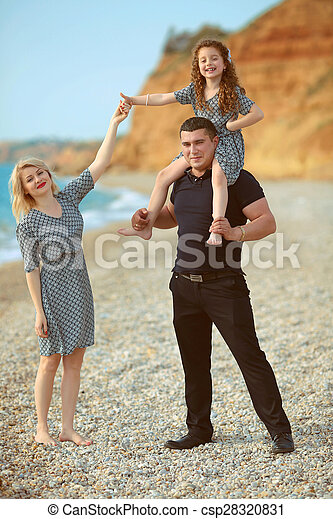 Happy Family Portrait On The Beach Father And Mother Walking With Their Funny Little Daughter At Stock Photo