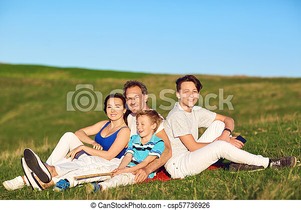 Happy family sitting on nature in spring, summer. - csp57736926