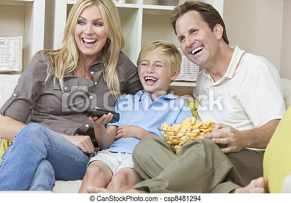 Happy Family Sitting on Sofa Laughing Watching Television - csp8481294