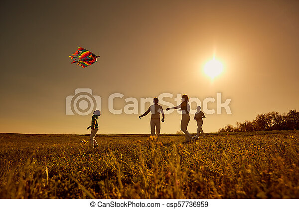 Happy family with a kite playing at sunset in the field - csp57736959