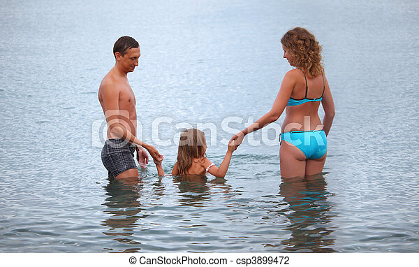 Happy family with little girl bathe in sea, standing back - csp3899472