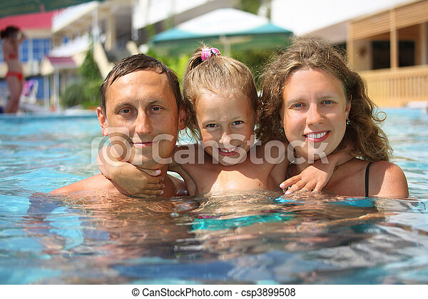 happy family with little girl in water hugging - csp3899508