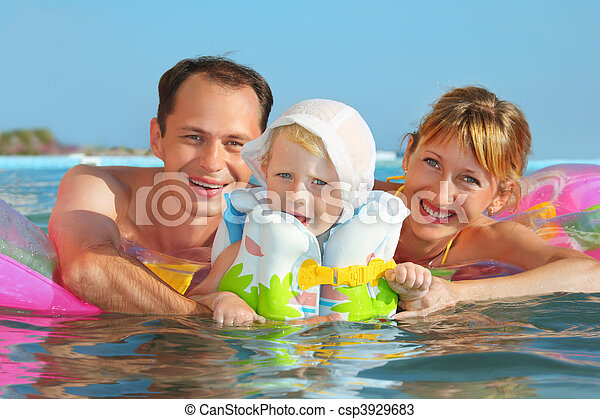 Happy family with little girl in white hat and lifejacket bathing in pool against sea - csp3929683