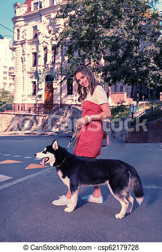 Happy family woman feeling joyful while walking with her black husky dog - csp62179728